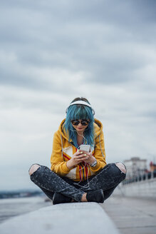 Young woman with dyed blue hair sitting on a wall listening music with headphones and smartphone - VPIF00856
