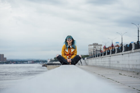 Young woman with dyed blue hair sitting on a wall - VPIF00859