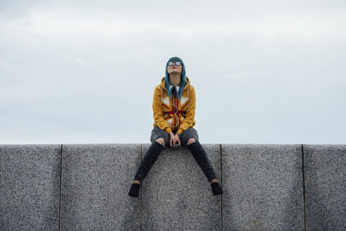 Young woman with dyed blue hair sitting on a wall looking up - VPIF00862