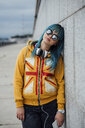 Portrait of young woman with dyed blue hair wearing mirrored sunglasses and fashionable hooded jacket - VPIF00865