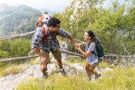 Italy, Massa, man helping a young woman to climb a step while hiking in the Alpi Apuane mountains - WPEF00852