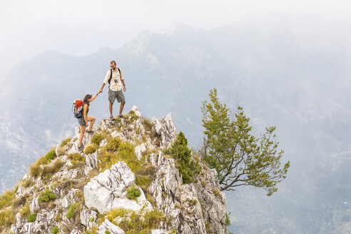 Italy, Massa, man helping woman to climb on top of a peak in the Alpi Apuane mountains - WPEF00858