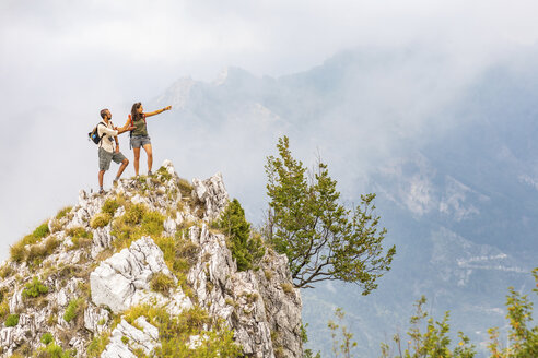 Italy, Massa, couple standing on top of a peak in the Alpi Apuane mountains - WPEF00861
