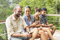 Italy, Massa, hikers in the Alpi Apuane mountains looking at their smartphones and sitting on a bench - WPEF00885
