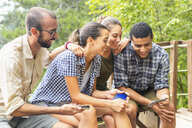 Italy, Massa, smiling hikers in the Alpi Apuane mountains looking at their smartphones and sitting on a bench - WPEF00888