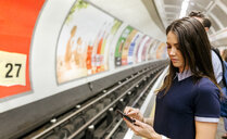 UK, London, young woman waiting at underground station platform looking at cell phone - MGOF03788