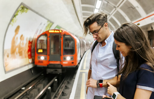 UK, London, couple waiting at   underground station platform looking at smartwatch - MGOF03791