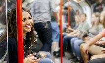 UK, London, portrait of smiling woman with cell phone sitting in underground train - MGOF03797