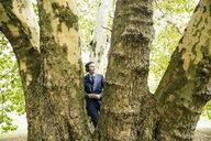 Businessman wearing headphones at a tree - MOEF01381