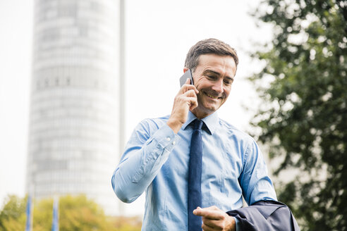 Smiling businessman on cell phone in city park - MOEF01390