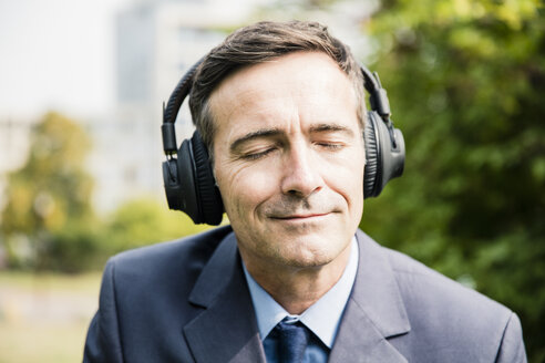 Businessman with closed eyes listening to music with headphones - MOEF01393