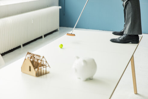 Close-up of businessman playing golf with piggy bank and house model on table in office - MOEF01396