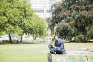 Businessman in city park wearing headphones and using tablet - MOEF01399