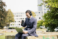 Businessman in city park wearing headphones and using laptop - MOEF01402