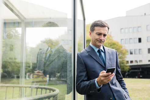 Serious businessman using cell phone leaning against glass front - MOEF01411