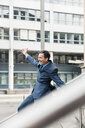 Carefree businessman sliding down railing in the city - MOEF01414