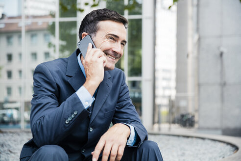 Smiling businessman on cell phone in the city - MOEF01420