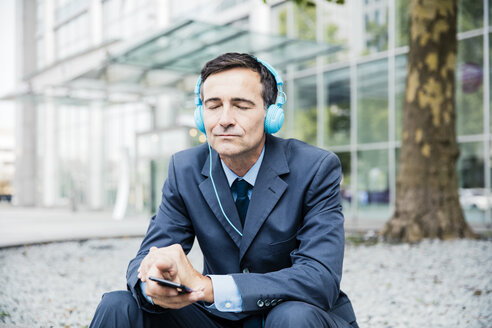 Businessman with closed eyes listening to music with headphones in the city - MOEF01423