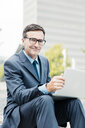 Portrait of smiling businessman sitting down using laptop in the city - MOEF01435