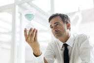 Serious businessman looking at hourglass in office - MOEF01456