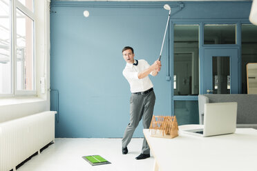 Businessman playing golf in office - MOEF01462