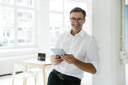 Portrait of happy businessman with tablet in bright office - MOEF01465