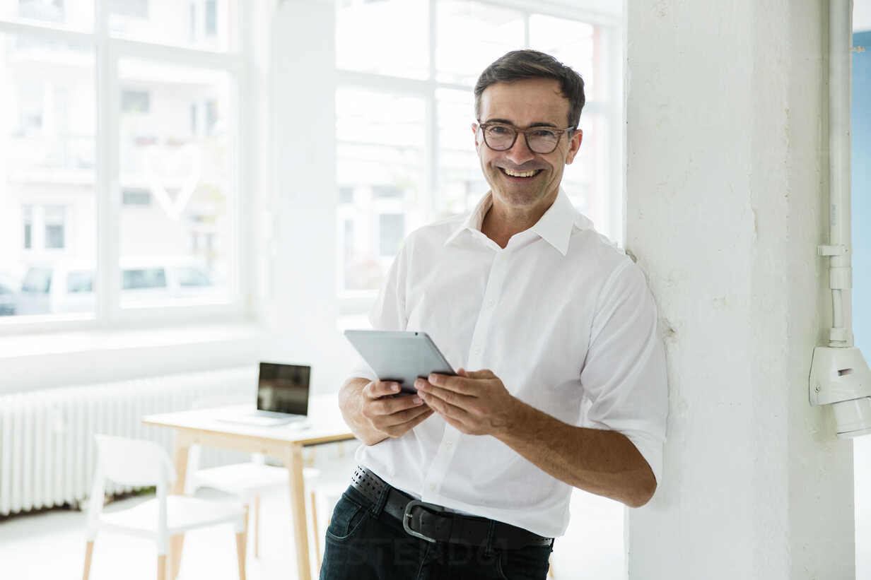 Portrait of happy businessman with tablet in bright office - MOEF01465 - Robijn Page/Westend61