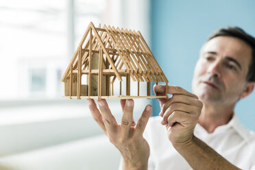 Businessman holding model house in office - MOEF01480