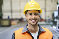 Portrait of smiling man wearing protective workwear in factory - BSZF00586