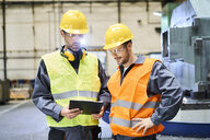 Two men wearing protective workwear holding clipboard and talking in factory - BSZF00589