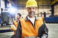 Portrait of smiling man wearing protective workwear in factory - BSZF00592