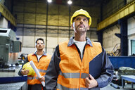 Two men wearing protective workwear looking around in factory - BSZF00595