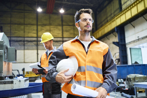Two men wearing protective workwear looking around in factory - BSZF00598