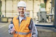 Portrait of smiling man holding blueprints in factory - BSZF00604