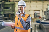Smiling man holding blueprints and using cell phone in factory - BSZF00607