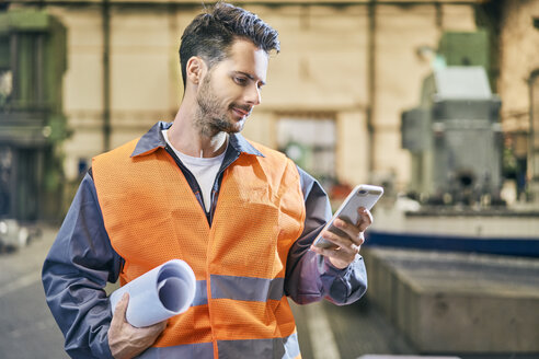 Smiling man holding blueprints and looking at cell phone in factory - BSZF00610