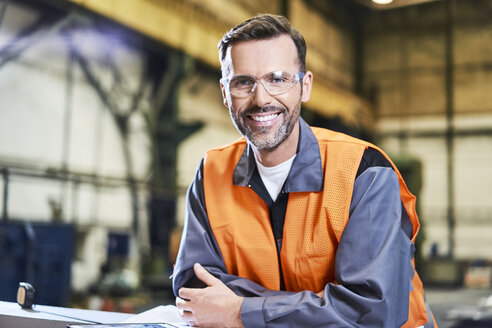 Portrait of smiling man in factory wearing protective glasses - BSZF00616