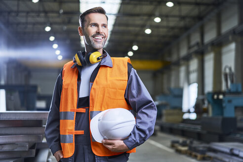 Portrait of smiling man wearing protective workwear in factory - BSZF00622