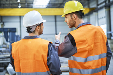 Rear view of two men wearing protective workwear talking in factory - BSZF00628