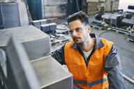 Man wearing protective workwear working in factory - BSZF00634