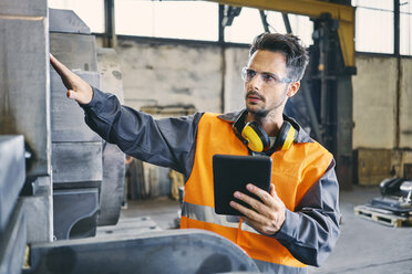 Man with tablet wearing protective workwear working in factory - BSZF00637