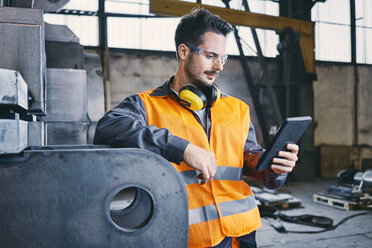 Man with tablet wearing protective workwear working in factory - BSZF00640