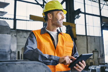 Smiling man with tablet wearing protective workwear in factory - BSZF00643