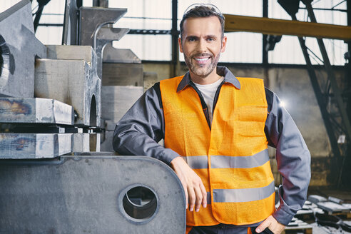 Portrait of smiling man wearing protective workwear in factory - BSZF00646