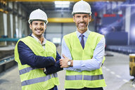 Portrait of two smiling managers wearing protective workwear in factory - BSZF00649