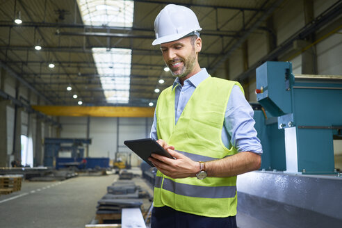 Smiling man wearing shirt and safety vest using tablet in factory - BSZF00658
