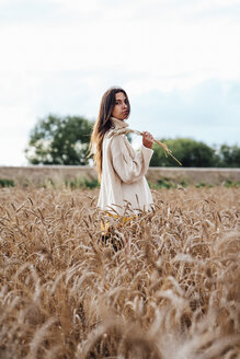 Young woman wearing oversized turtleneck pullover standing in corn field - VPIF00881
