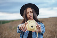 Portrait of young woman taking photo of viewer - VPIF00887