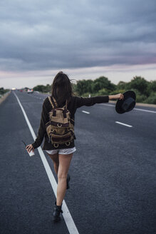 Back view of hitchhiking young woman with backpack and beverage standing at side line - VPIF00902