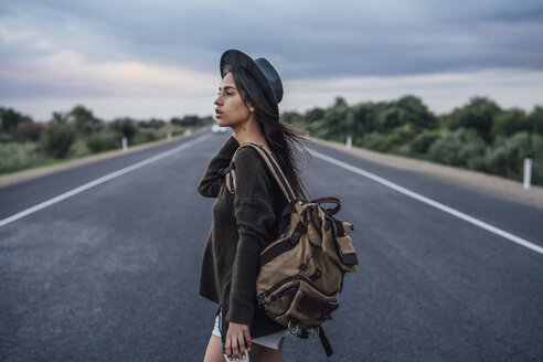 Portrait of hitchhiking young woman with backpack and beverage on lane - VPIF00905